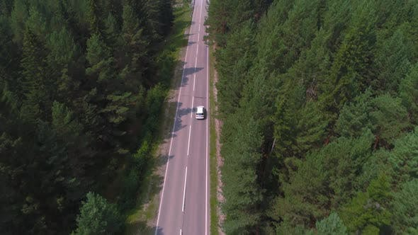 AERIAL Dark Colored Car Driving Down an Asphalt Road Crossing the Vast Forest on a Sunny Summer Day