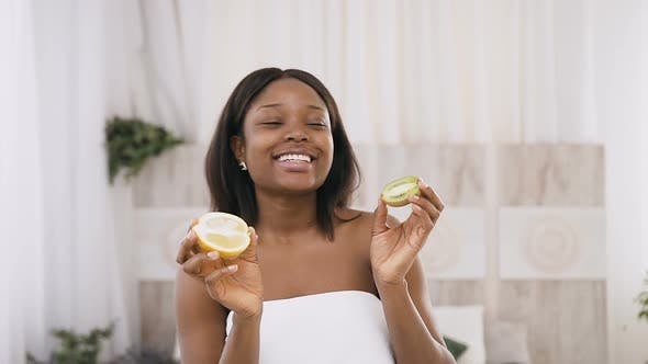 Thumbnail for Funny Amusing African American Young Woman Holding Kiwi and Orange Halves in Hands Over Light