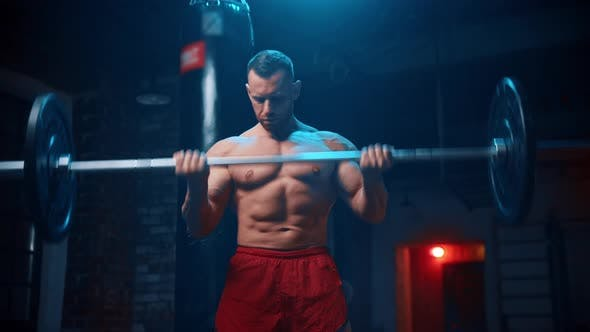 Strong Man Standing in the Gym and Lifts a Heavy Bar and Pumping His Hands Muscles