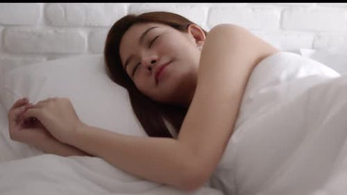 Asian women sleeping and sweet dream on white bed in bedroom