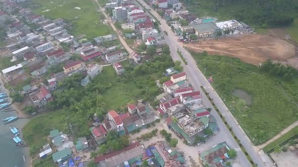 Asphalt Road Runs Along Lively Village Located on River Bank