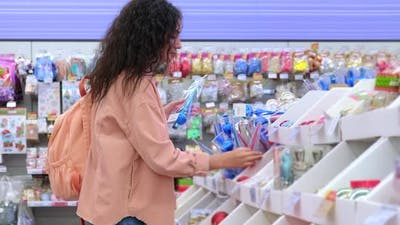 Woman Choosing Christmas Ornaments in the Hypermarket