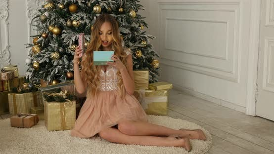Thumbnail for Beauty Girl Opens Christmas Gift Box with Miracle Lights. Surprised Woman Getting Magic Gift