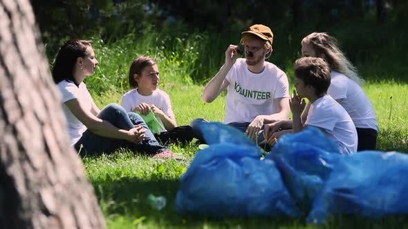 Volunteers Sit on Lawn Family Recycle Plastic Bottle with Bags Full of Trash Resting and Talking