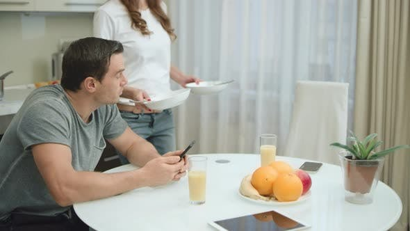 Thumbnail for Happy Couple Eating Healthy Breakfast at Luxury Home. Man Looking Mobile Phone
