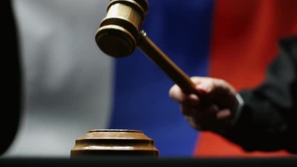 Thumbnail for Judge With Gavel In His Hand Hammering Against Waving Russian Flag in Courtroom