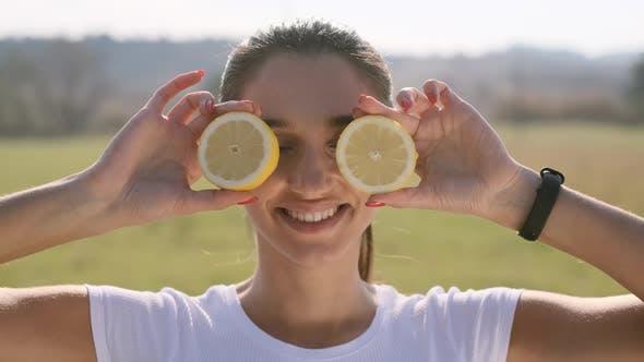 Thumbnail for Mädchen steht auf dem Feld Mit Zitrone In Ihre Hände
