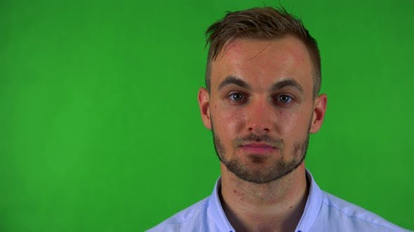 Thumbnail for Young Handsome Business Man Looks To Camera with Serious Face - Green Screen - Studio - Closeup