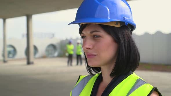Architect woman confidently looking at camera at construction site