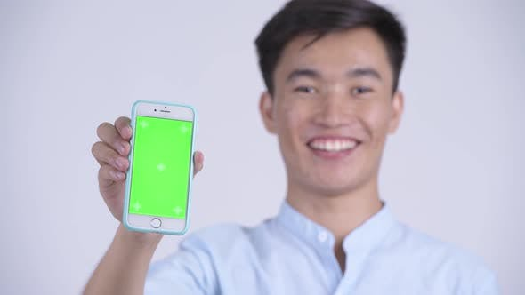 Cover Image for Face of Young Happy Asian Businessman Showing Phone