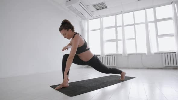 Thumbnail for Woman practicing yoga and stretching exercises in white loft hall, female stretch her body and legs