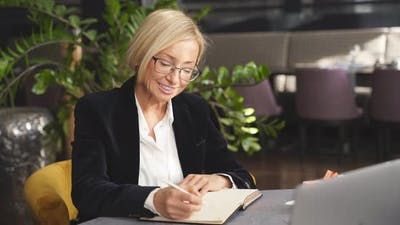 Beautiful Blond Business Lady Sitting at a Table During Business Meeting