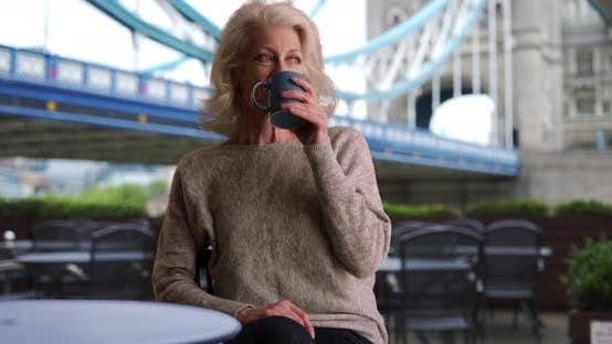 Thumbnail for Attractive senior woman sitting on outdoor cafe patio by Tower bridge in London