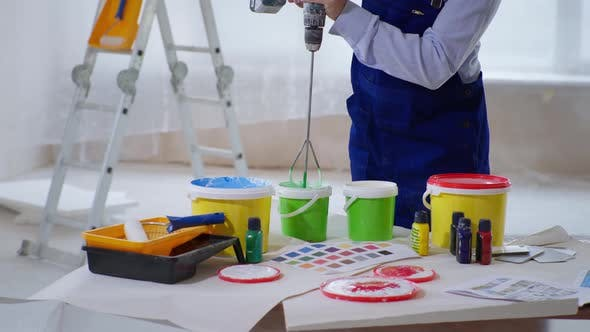 Thumbnail for Male Painter Mixes Paint in Bucket with Construction Mixer for Painting Walls Indoors