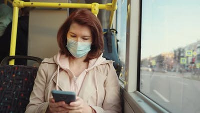 Woman in Mask Using Smartphone in Bus