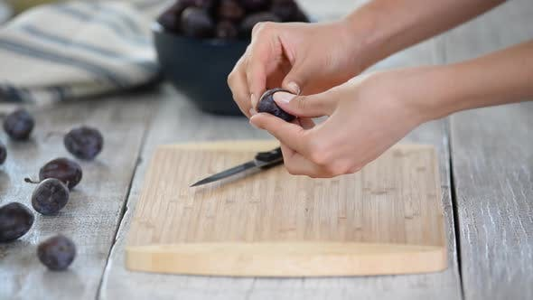 Thumbnail for Woman cooking and cutting plum on wooden cutting board. Preparing healthy food.