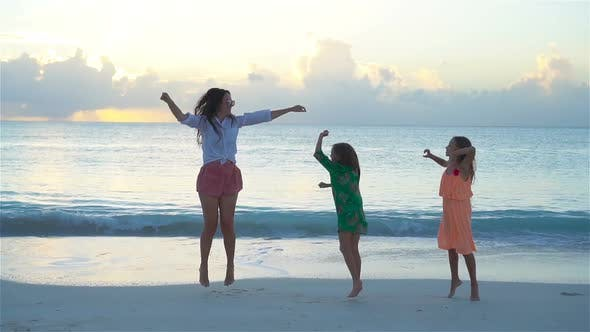 Thumbnail for Little Adorable Girls and Young Mother at Tropical Beach in Warm Evening Dancing and Having Fun