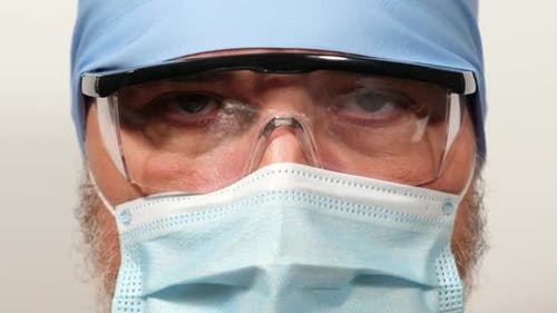 doctor in a textile cap, protective transparent glasses