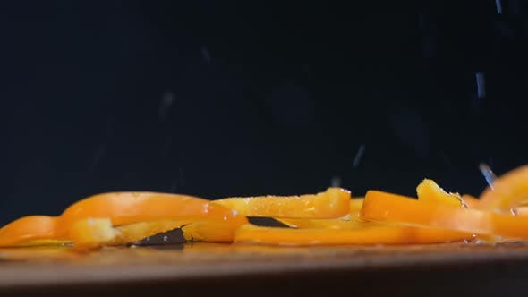 Yellow Bell Pepper Slices Fall on Brown Board with Water
