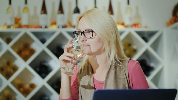 Thumbnail for Business Woman Tasting Wine in a Small Cozy Cafe, Looking at the Laptop Screen