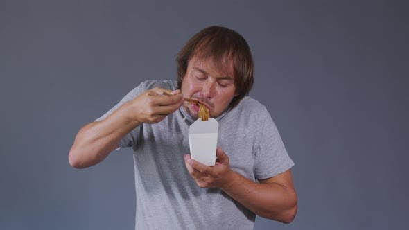 Thumbnail for Man Relish Is Eating Food. Smiling Men Holding White Box with Chinese Noodles.