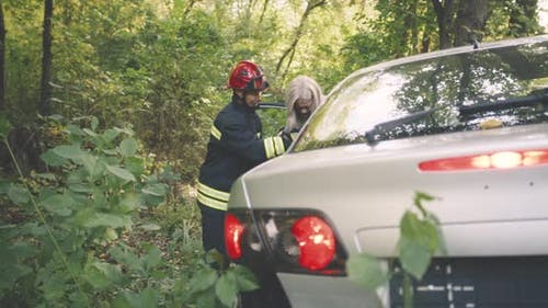 Firefighters Saving People From Wrecked Car