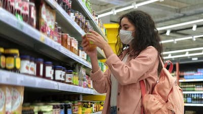 Young Woman with Face Mask is Buying Honey or Jam in Supermarket