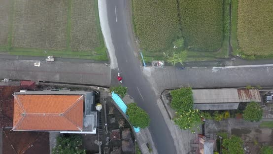 Aerial drone view of a man riding his motocross motorcycle on a road in Bali
