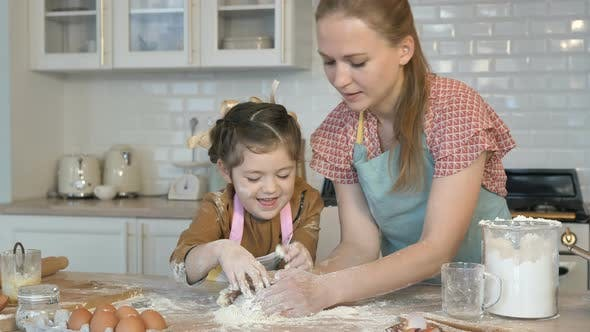 Thumbnail for Happy Mother and Daughter Cook Together in the Kitchen, Knead the Dough. The Daughter Laughs and