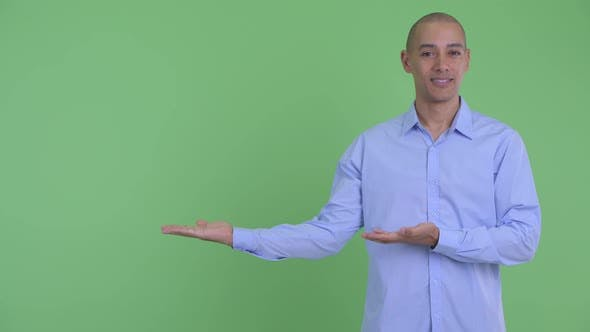 Happy Bald Multi Ethnic Businessman Showing Something and Giving Thumbs Up