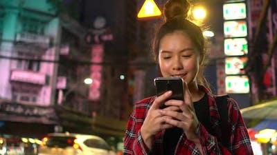 Woman holding smartphone on night street