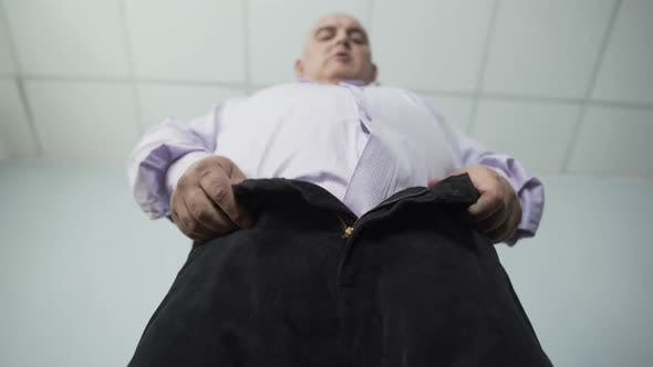 Thumbnail for Base View Of Overweight Man Trying Hard To Zip Tight Pants, Disappointment