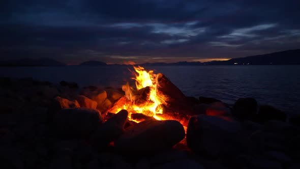 Thumbnail for View of campfire on the side of a lake at dusk