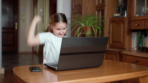 A little cute girl looks at the laptop screen and is excited by luck and success