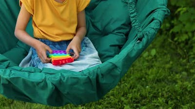 A Little Girl the on Hanging Chair Outdoors Play Pop It Kid Hands Playing