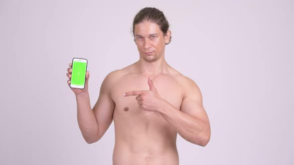Thumbnail for Happy Muscular Shirtless Man Showing Phone and Giving Thumbs Up