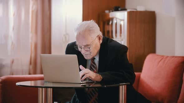 Thumbnail for Elderly Grandfather - Old Grandfather Is Typing Something Hunched Over a Computer