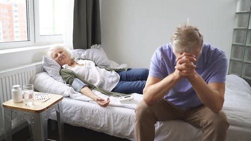 Mature Woman Sleeps on the Bed and the Husband Sits Next To Her and Worries About His Wife Because