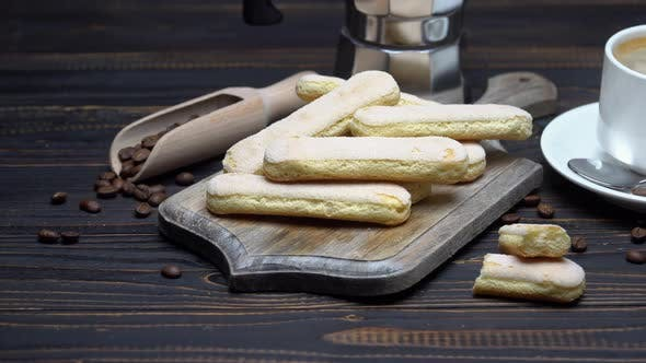 Cover Image for Italian Savoiardi Ladyfingers Biscuits and Cup of Coffee on Wooden Background