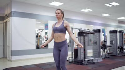 Young woman with jumping rope in fitness center
