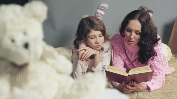 Thumbnail for Mom and Daughter Comfortably Lying in Bed Reading Fairy Tales and Dreaming