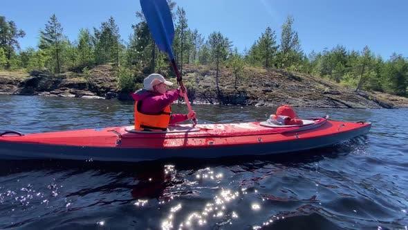 Frau Rows Sport Kajak mit Kind entlang des ruhigen Flusses