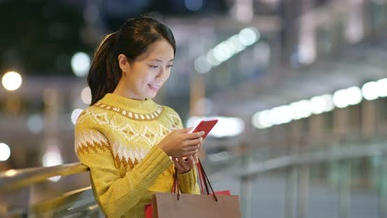 Thumbnail for Woman holding with shopping bag and use of smart phone in city