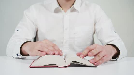 Thumbnail for Person, die ein Buch auf dem Schreibtisch liest