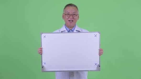 Thumbnail for Happy Mature Japanese Man Doctor Talking While Holding White Board