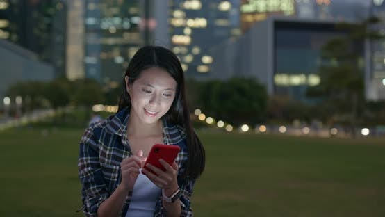 Cover Image for Woman check on mobile phone at outdoor in city at night