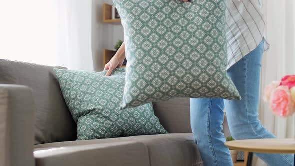 Woman Arranging Cushions at Home