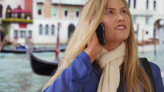 Smiling Caucasian female talks on cellphone while sightseeing in Venice