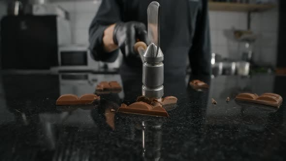 Thumbnail for Chef Chocolatier Smashes the Milk Chocolate Bar By Kitchen Hammer on the Marble Table in Slow Motion