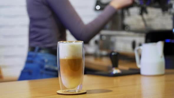 Thumbnail for Cappuccino or latte in glass. Woman puts drink from coffee machine.
